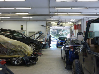 photo of cars in shop in various stages of repair